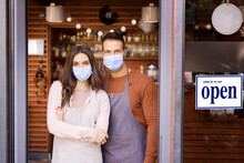 Proud Restaurant Owners Wearing Face Mask For Prevention While Standing In The Doorway And Waiting For Guests
