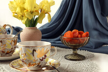 Dried Apricots In A Glass Vase With A Bouquet Of Yellow Irises, Tea Cups On A Gray Background With A Light Scarf, Side View-the Concept Of A Wonderful Time With A Cup Of Tea