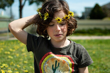 Portrait Of Young Child Wearing A Daisy Chain Made Of Capeweed