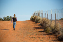 Person Walking Away Along Rabbit Proof Fence