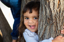 Little Girl Looking At Camera From Behind Tree