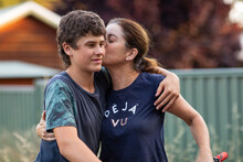 Mother Kissing Teenaged Son On The Cheek