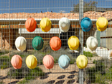 Hard Hats On Fence At A Touris...