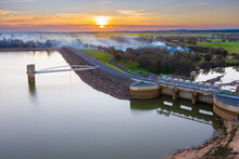 Aerial View Of A Water Tower In A Reservoir At Sunset With Smoke Drifting Across.