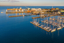 Aerial View Of A Bay Side Yacht Club With Rows Of Boats Lined Up Along Jetties