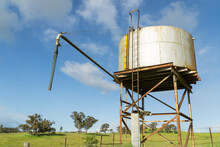 A Water Tank Sitting On A High Metal Stand In A Paddock