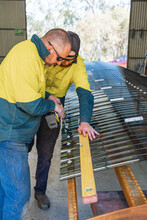 Two Tradesmen Cooperating To Attach Corrugated Screening To An Awning