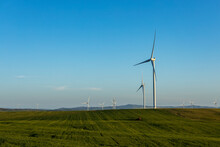 Wind Towers In Late Afternoon With Farmland In Foreground