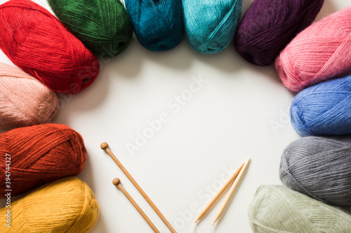 Fotografía Colored yarn balls and knitting needles on white