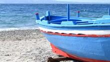 Redandwhitebluehullofafisherman'sboatfromsouthernItalyonthebeachonadayofstrongwindandslightlychoppysea - Real Time 4K