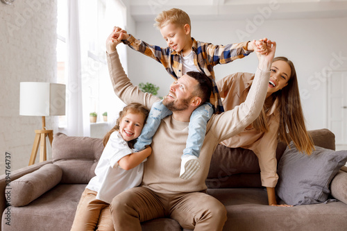 Fototapeta happy family mother father and kids having fun at home on couch . obraz