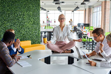 Female Office Worker Is Meditating, Taking Break At Work For Mental Balance While Others Work. Mindful Businesswoman Feeling Relief And No Stress Doing Yoga At Work Ignoring Avoiding Stressful Job