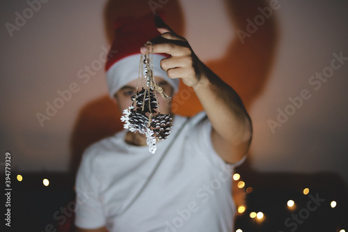 Cuadros en Lienzo Person in a white T-shirt and a Christmas hat on his head shows decorations on the Christmas tree