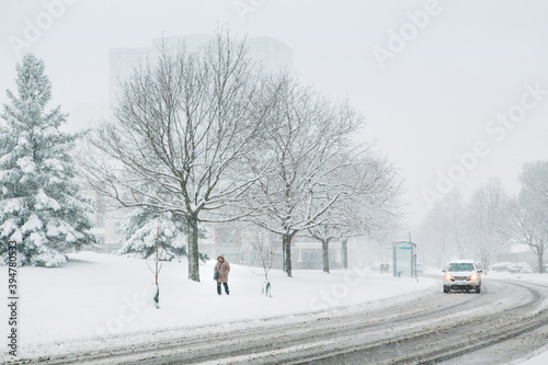 Fototapeta premium Man walking under snow. Heavy snowfall and snowstorm in Toronto, Ontario, Canada. Snow blizzard and bad weather winter condition. Poor visibility, seasonal danger for drivers on streets.