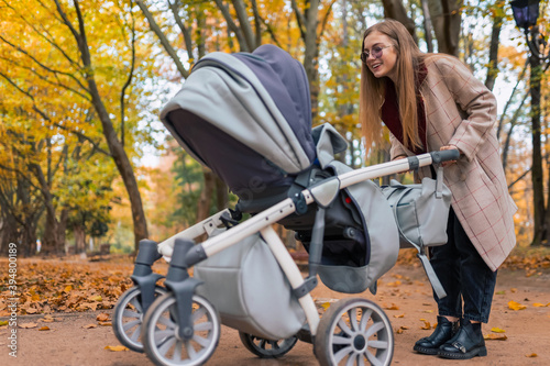 Canvas Print Cheerful mom playing with newborn baby in stroller