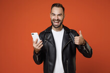 Cheerful Young Bearded Man In Basic White T-shirt Black Leather Jacket Standing Using Mobile Cell Phone Typing Sms Message Showing Thumb Up Isolated On Bright Orange Colour Background Studio Portrait.