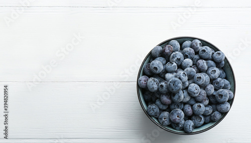 Photo Tasty frozen blueberries in bowl on white wooden table, top view