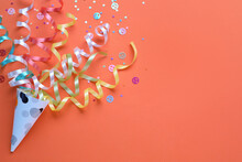 Colorful Confetti And Streamers With Party Cracker On Orange Background, Top View. Space For Text