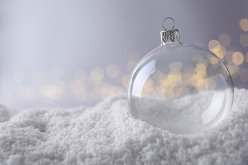 Transparent Christmas ball on snow against blurred fairy lights, space for text