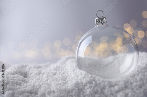 Vászonkép Transparent Christmas ball on snow against blurred fairy lights, space for text