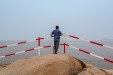 A Chinese Male Tourist Standing On Rocks And Looking At The Sea In Putuoshan, Zhoushan Islands,  A Renowned Site In Chinese Bodhimanda Of The Bodhisattva Avalokitesvara (Guanyin)