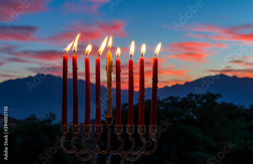 Glitter lights of candles on menorah are traditional symbols for Jewish Hanukkah Holiday of Light. Selective focus on candles. Background with blurred dramatic morning sky and mountains as background