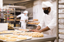 Male Baker In Mask And White Uniform Rolling Out Dough In Kitchen