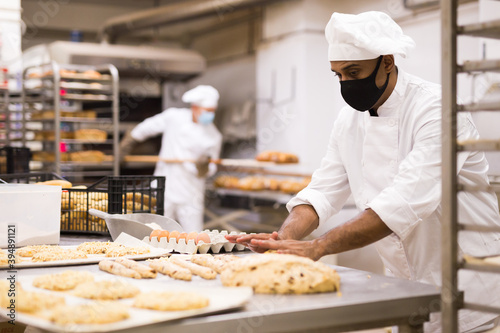 Fotografie, Obraz male baker in mask and white uniform rolling out dough in kitchen