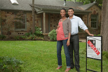 Couple Standing In Yard With Sold Sign