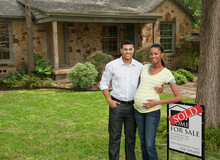 Couple Standing In Yard Next To Sold Sign