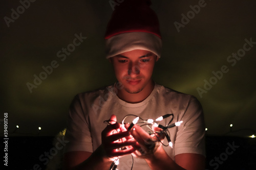 Fotografia Young man enjoys the atmosphere of a real European Christmas and smiles over small lights that he fixes on a Christmas tree