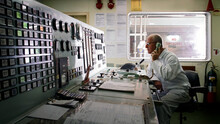 Senior Engineer Taking Phone Instructions Whilst Monitoring Controls In Ship's Engine Room.