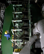 Aerial View Of Engineer With Maintenance Chart In Ships Engine Room Conducting A Check