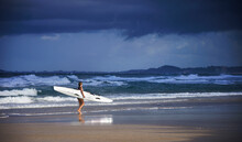 Side On View Of Female Surf Lifeguard Training Walking Along The Beach Holding Ocean Surf Ski With Rough Waves And Stormy Sky