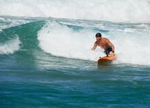 Male Surf Lifesaver Riding A Wave On Ocean Surf Ski