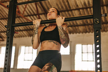 Woman Doing Pull Up Workout In Empty Factory Shade
