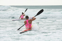 Back View Of Male And Female Surf Lifesaver Paddling Through Waves On Ocean Surf Ski