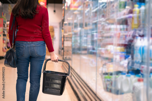 Fototapeta Cheerful Asian young woman holding a shopping basket in the supermarket obraz