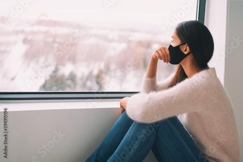 Sad woman alone during coronavirus pandemic wearing face mask indoors at home for social distancing. Anxiety, stress, mental health crisis.