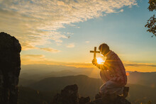 Silhouette Of A Young Christian Man Who Is Praying On The Holy Cell In The Bible And Raising A Cross Over A Christian With A Light Sunset Background. Christian Concept