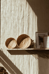Modern boho style home interior design. Bohemian decoration accessories: photo frames, straw plates on wooden shelf on concrete wall. Sunlight silhouette shadows on the wall. Vintage retro concept.