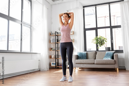 sport, fitness and healthy lifestyle concept - smiling young woman stretching ar Billede på lærred