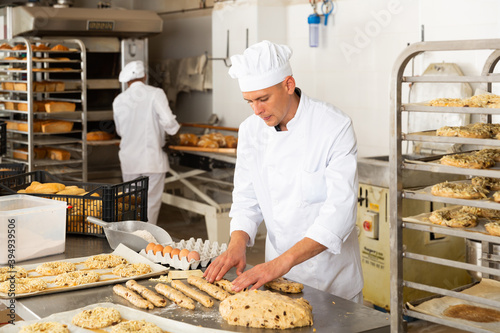 Fototapeta Working at bakery, male baker kneading dough and shaping baguettes on steel coun
