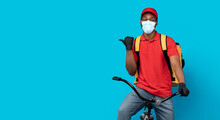 African American Delivery Guy In Medical Mask Pointing Away