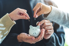 Closeup Image Of People Holding And Putting Coin Into Piggy Bank For Saving Money And Financial Concept