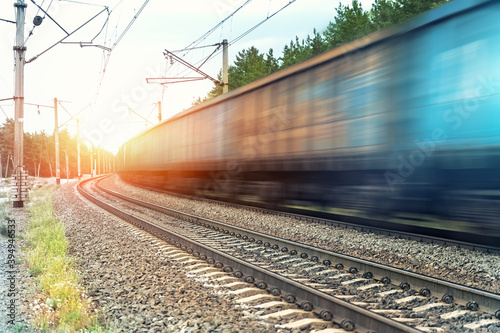 Fotografie, Obraz Motion blurred heavy cargo freight rusty train wagons moving on railway on sunset or sunrise day time