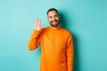 Photo Of Friendly Young Man Saying Hello, Smiling And Waiving Hand, Greeting You, Standing In Orange Sweater Over Light Blue Background