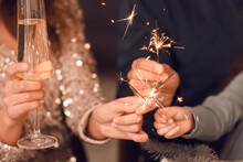 Happy Family With Sparklers And Champagne Celebrating Christmas At Home, Closeup
