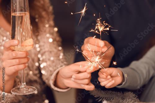 Fotografija Happy family with sparklers and champagne celebrating Christmas at home, closeup