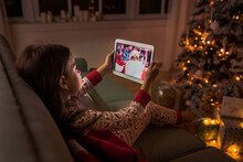 Child Girl Talking To Santa Claus By Video Call On Tablet On Christmas Eve At Home. New Normal Celebration Of The Holidays During  Pandemic.